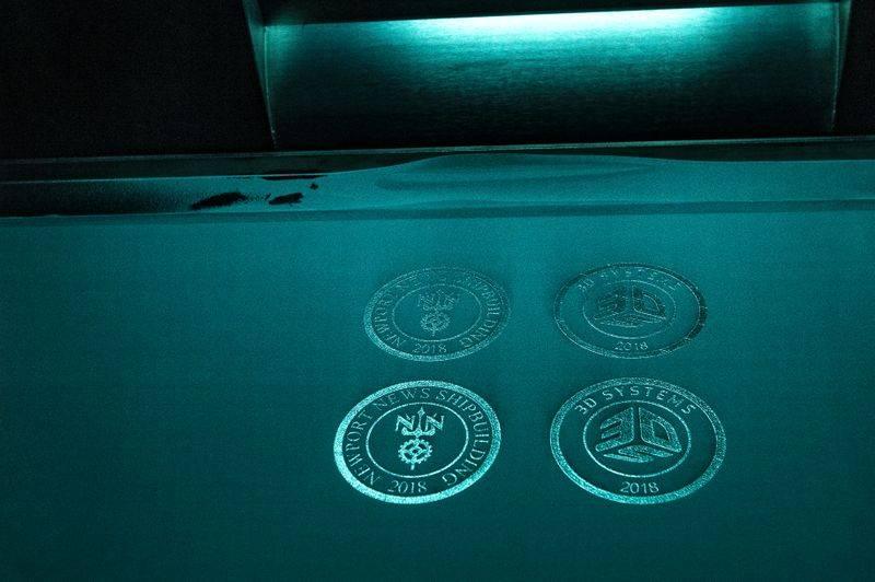 Τα λογότυπα από την Newport News Shipbuilding και τα 3D συστήματα κατασκευάστηκαν κατά τη διάρκεια της επίδειξης του νέου εκτυπωτή 3-D. (Φωτογραφία από John Whalen / HII)