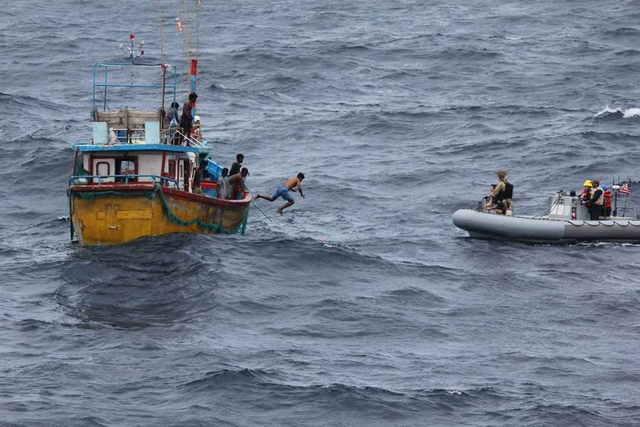 Рыбак Шри-Ланки прыгает и плавает на надувной лодке с жестким корпусом из эскадренного миноносца управляемой ракеты Arleigh Burke USS Decatur (DDG 73) после того, как корабль остановился, чтобы оказать помощь рыболовецкому судну. (Фото ВМС США)