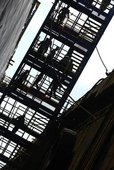 العمال يشقون طريقهم على طول السقالات خلال غداء على متن سفينة Kaimana Hila ، وهي حاوية بحجم 850 قدم يجري بناؤها في Philadelphia Shipyards. أثناء البناء ، يعمل خفر السواحل مع شركة بناء السفن وشركة الشحن والمسجل في جهد موحد لجعل السفينة آمنة قدر الإمكان للتشغيل. (صور خفر السواحل سيث جونسون)