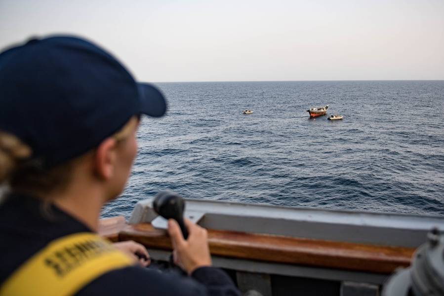 يختبئ سلاح البحرية الأمريكي من جناح الجسر في يو إس اس جيسون دونهام (DDG 109) بينما يقوم فريق السفينة والزوار والمجلس والبحث ومصادرة السفن بتفتيش مركب شراعي. (صورة للبحرية الأمريكية من قبل جوناثان كلاي)