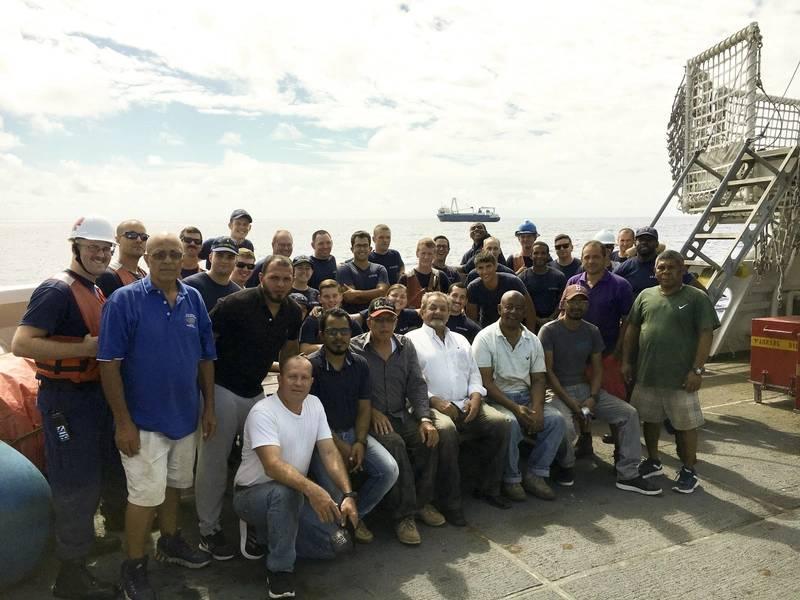 कोस्ट गार्ड कटर कॉन्फिडेंस के कुछ दल मालवाहक जहाज अल्ता से बचाए गए पुरुषों के साथ इकट्ठा होते हैं। (टोड बेहनी द्वारा यूएस कोस्ट गार्ड फोटो)