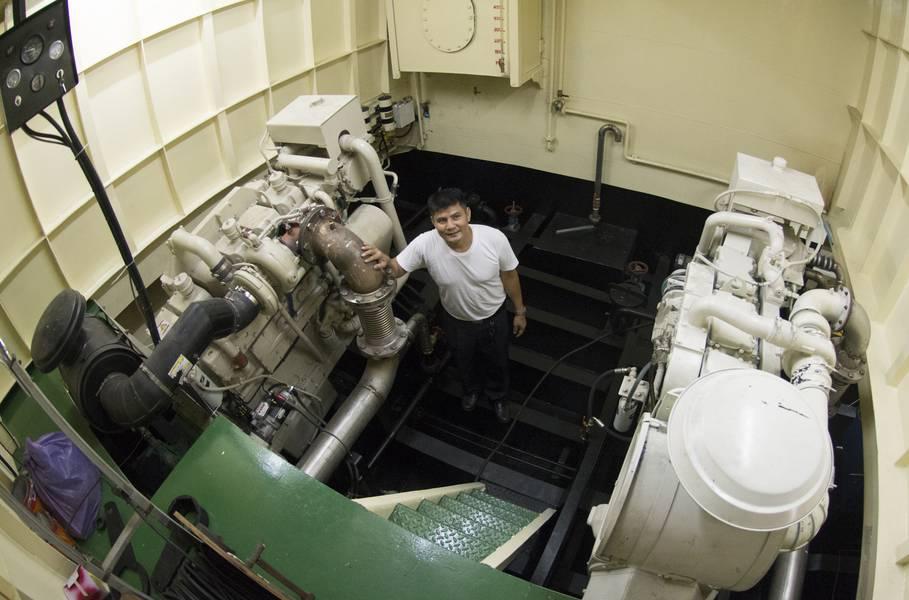 पोर्ट कैप्टन मिटर डाईवॉन्ग 600 एचपी, कमिन्स केटीए 1 9-एम मुख्य इंजनों में से एक के साथ पोर्ट-साइट इंजन रूम में खड़े हैं। NT855 150 किलोवाट जेनेटसेट बाईं ओर है। (फोटो क्रेडिट: हैग-ब्राउन / कमिन्स समुद्री)