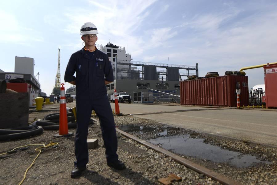 特拉华湾海岸警卫队的海洋检查员Lt. jg Ryan Thomas,在费城造船厂建造的850英尺集装箱船Daniel K. Inouye前面。 (海岸卫队摄影:Seth Johnson)