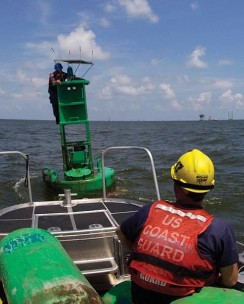 Aids to Navigation Teammitglieder aus Dulac, La., Richten ein Solarpanel aus, das das Beleuchtungssystem der Hilfe auflädt. US-Küstenwache Foto von Petty Officer 3. Klasse Thomas Atkeson.