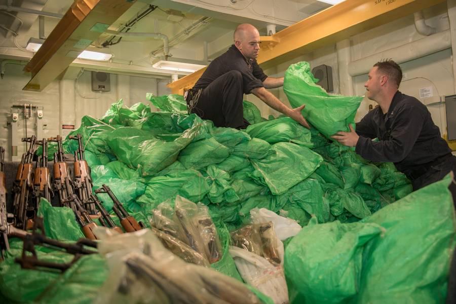 Marinheiros da Marinha dos EUA empilham um esconderijo de fuzis automáticos AK-47 a bordo do destróier de mísseis guiados USS Jason Dunham (DDG 109). (Foto da Marinha dos EUA por Jonathan Clay)