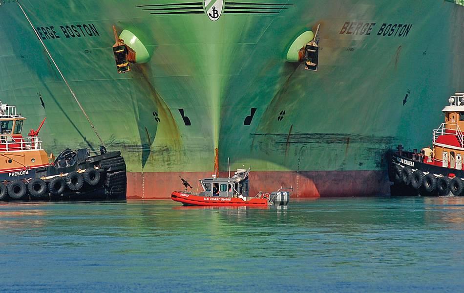 Mientras proporciona un perímetro de seguridad, un bote de respuesta de 25 pies de la Guardia Costera está flanqueado por dos remolcadores cuando el petrolero de gas natural líquido Berge Boston está amarrado al muelle en una instalación de GNL aquí. Foto de USCG por PA2 Luke Pinneo