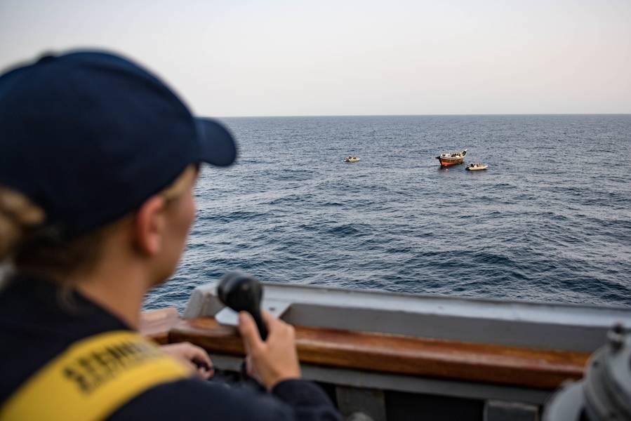 Um alferes da Marinha dos EUA conecta-se com a asa da ponte do USS Jason Dunham (DDG 109) enquanto a equipe de visita, placa, busca e apreensão do navio inspeciona um dhow. (Foto da Marinha dos EUA por Jonathan Clay)