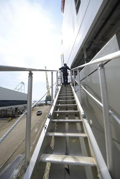 El teniente J. Ryan Thomas, un inspector de marina en el sector de la Guardia Costera de Delaware, camina por la pasarela del Daniel K. Inouye, un portacontenedores que se está construyendo en los Astilleros de Filadelfia. (Foto de la Guardia Costera por Seth Johnson)