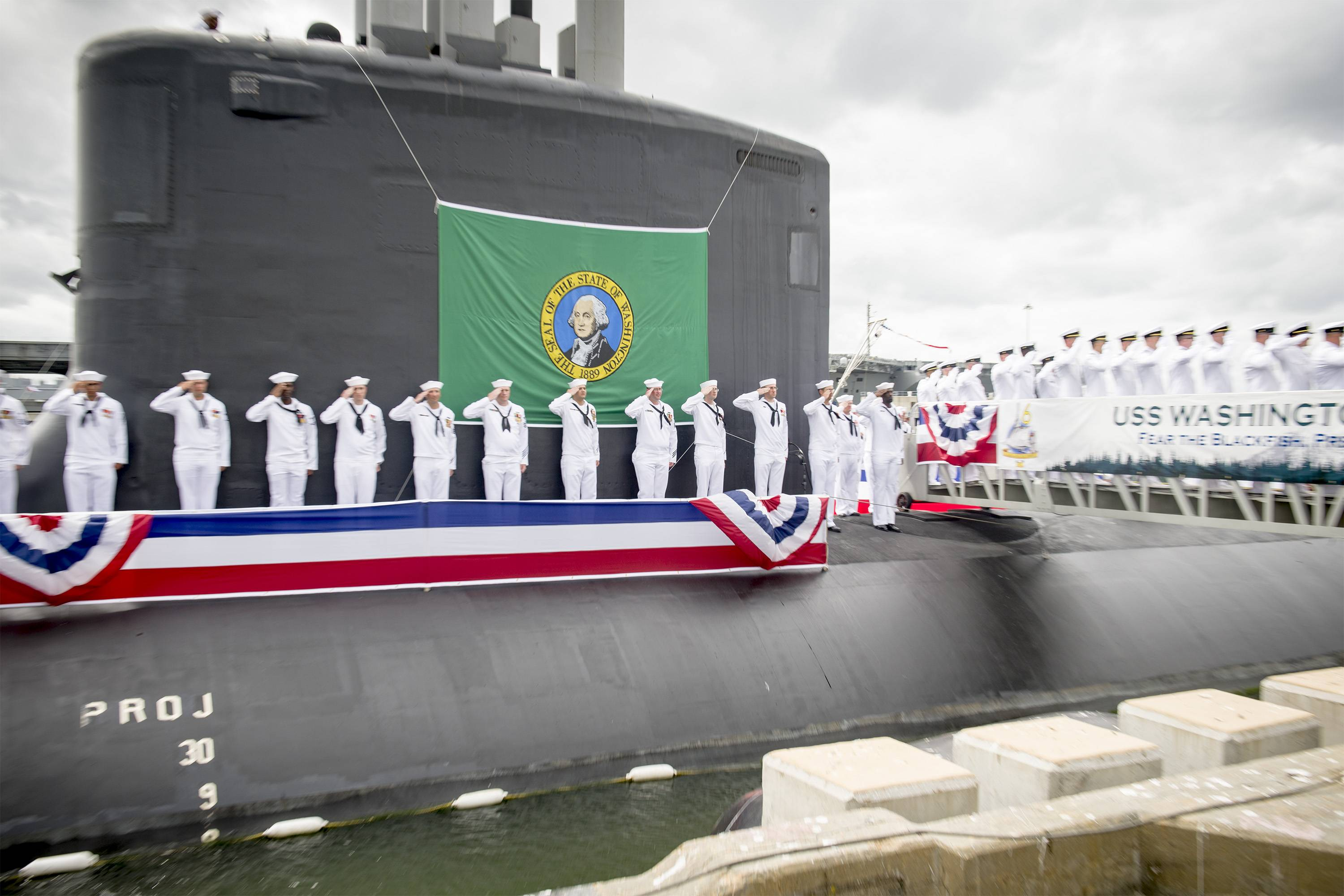 Sailors render a salute during the commissioning ceremony for the Virginia Class Submarine USS Washington at Naval Station Norfolk. Washington is the U.S. Navy's 14th Virginia-class attack submarine and the fourth U.S. Navy ship named for