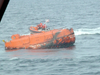 A crew from the Coast Guard Cutter Shearwater approaches a capsized lifeboat from the Bow Mariner. U.S. COAST GUARD PHOTO