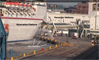 Screen shot from a CCTV monitor, provided to the NTSB by the U.S. Coast Guard, shows the allision of the Carnival Pride with the pier at Cruise Maryland Terminal, South Locust Point, Baltimore Harbor, Md., as the elevated passenger embarkation walkway falls and crushes three vehicles parked below on the pier (Photo: USCG / NTSB)