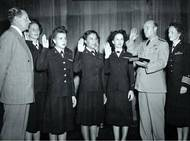 The first six enlisted women are: Front row: (left to right) Chief Yeoman Wilma J. Marchal, USN; Yeoman Second Class Edna E. Young, USN; Hospital Corpsman First Class Ruth Flora, USN Second row: (left to right) Aviation Storekeeper First Class Kay L. Langen, USN; (hidden behind the front row): Storekeeper Second Class Frances T. Devaney, USN; and Teleman Doris R. Robertson, USN. (NHHC Photo)