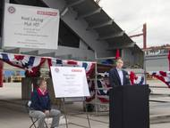 Steve Becker, vice president of Great Lakes Dredge & Dock Company, joins Victor Rhoades (seated), director and general manager of BAE Systems Southeast Shipyards, at a recent keel laying ceremony for the first of two dump scows under construction at BAE Systems' Mobile, Alabama facility.