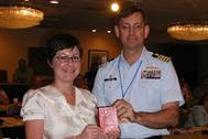 Jessica Dennis, regulatory compliance manager for Hornbeck Offshore, receives the first new consolidated Merchant Mariner Credential from Capt. David Stalfort, commanding officer of the National Maritime Center, during the Towing Safety Advisory Committee meeting held Thursday, May 7, 2009, at Dania Beach, Fla. (U.S. Coast Guard photo/U.S. Coast Guard)