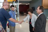 Apprentices Jason Marshall (left) and Matthew Stanley (center) greet Virginia Secretary of Education Anne Holton in the lobby of The Apprentice School before her tour led by the school's director, Everett Jordan (right). Photo by Chris Oxley/HII