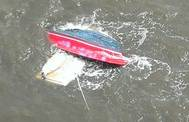 A personal craft is capsized after a collision with a tug and barge Sunday. U.S. Coast Guard photo.