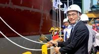 Takaaki Anraku, President Kokusai Cable Ship Company Ltd of Japan, cutting the rope to break the milk pot against the vessel's hull. Photo: Colombo Dockyard PLC