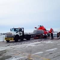 A Dolphin helicopter from Coast Guard Air Station Traverse City, Mich., arrives at Northport Pier in Door County, Wis., on a flatbed trailer March 3, 2014 following a brief ferry transit from Washington Island. (USCG photo)