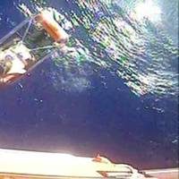 A helicopter rescues one of 12 crewmembers who abandoned ship in Cuban territorial seas December 26. Two USCG helicopter crews responded and subsequently rescued all 12 crewmembers from the sinking 120-foot coastal freighter. (Screenshot from USCG video)