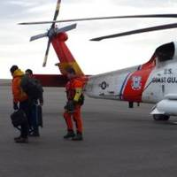 A man suffering from a head injury walks toward an ambulance after being medevaced from a South Korean icebreaker by a Coast Guard MH-60 Jayhawk helicopter crew to Barrow, Alaska, Aug. 20, 2014. (USCG photo)