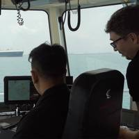 A PSA Marine Tug Master and Thomas monitoring how the smart navigation system maneuvers the harbor tug during sea trials. (Photo: Wärtsilä)