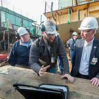 Aaron Wikle (left), a pipefitter at Newport News Shipbuilding, shows Rep. Joe Courtney how the shipyard is presenting work to shipbuilders in a visual environment with the goal of improving quality and cost performance. (Photo by Chris Oxley/HII)
