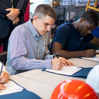Alma Bryant High School seniors (left to right) Tyler Morgan, Logan Lyons and Thomas Durgin sign paperwork, officially accepting positions at Ingalls Shipbuilding. HII photo