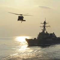 An MH-60S Knighthawk helicopter flies by the guided-missile destroyer USS Farragut in 2012 (U.S. Navy photo)