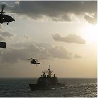 """An MH-60S Sea Hawk helicopter, assigned to the """"Sea Knights"""" of Helicopter Sea Combat Squadron (HSC) 22, transports supplies over the guided-missile cruiser USS Gettysburg (CG 64) during a replenishment-at-sea with the aircraft carrier USS Harry S. Truman (CVN 75) in the Arabian Gulf. (U.S. Navy photo by Seaman Karl Anderson)"""