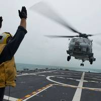Boatswain's Mate 2nd Class Adam Garnett signals an MH-60R Sea Hawk helicopter from Helicopter Maritime Strike Squadron (HSM) 35 on the flight deck of the littoral combat ship USS Fort Worth (LCS 3). Fort Worth is currently on station conducting helicopter search and recovery operations as part of the Indonesian-led efforts to locate missing AirAsia Flight QZ8501. (U.S. Navy photo by Antonio P. Turretto Ramos)