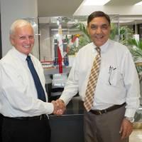 Bob Fogal, left, accepting congratulations from Ramesh Maini