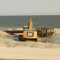 Bulldozers reconstruct the beach and dunes at Long Beach Island, New Jersey, as a dredge ship pumps sand from the Outer Continental Shelf to shore. Photo BOEM