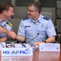 Capt. Greg Rothrock, Coast Guard Research and Development Center commanding officer, and Maj. Gen. William Cooley, Air Force Research Laboratory commander, shake hands after they signed a memorandum of understand between their two organizations. The agreement allows USCG RDC and AFRL to work together on tasks of mutual benefit. (U.S. Air Force photo by R.J. Oriez)