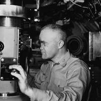 Captain Edward L Beach, USN, Commanding Officer of the nuclear submarine Triton (SSRN-586), at the periscope of his ship during her shakedown cruise around the world submerged. (U.S. Navy photo courtesy of the Bettmann collection)