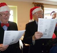 Commander Brian Boxall-Hunt OBE, Chief Executive of the Society and Capt. Braithwaite singing carols.