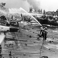 Crew members fight a series of fires and explosions on the carrier's after flight deck, in the Gulf of Tonkin, July 29, 1967. The conflagration took place as heavily-armed and fueled aircraft were being prepared for combat missions over North Vietnam. (Official U.S. Navy Photograph.)