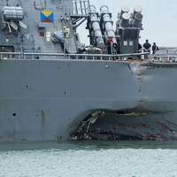 Damage to the portside is visible as the guided-missile destroyer USS John S. McCain (DDG 56) steers towards Changi Naval Base, Republic of Singapore, following a collision with the merchant vessel Alnic MC while underway east of the Straits of Malacca and Singapore. Significant damage to the hull resulted in flooding to nearby compartments, including crew berthing, machinery, and communications rooms. Damage control efforts by the crew halted further flooding. (U.S. Navy photo by Mass Communica