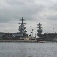 The aircraft carrier Pre-Commissioning Unit (PCU) Gerald R. Ford (PCU 78), left, and USS Dwight D. Eisenhower (CVN 69) sit pierside at Naval Station Norfolk. (U.S. Navy photo by Nathan T. Beard)