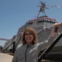 """Former U.S. Rep. Gabrielle """"Gabby"""" Giffords waves to a crowd in front of the littoral combat ship, USS Gabrielle Giffords (LCS 10). (Photo courtesy Austal USA/Released)"""
