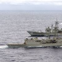 HMAS Newcastle and HMAS Melbourne pass each other as Melbourne takes over from Newcastle as the Australian ship assigned to Operation SLIPPER. (Credit: LA Richard Close)
