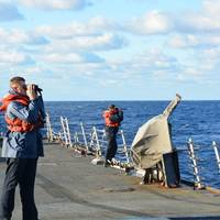 Sailors aboard the guided-missile destroyer USS Mason (DDG 87) keep lookout while searching for a sailor missing overboard from the cruiser USS Normandy (CG 60). (U.S. Navy photo by Jef Van Hoof)