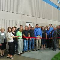Joined by Jet Edge employees and local business and government leaders, Jet Edge President Jude Lague cuts a ribbon to mark Jet Edge's 30th anniversary in the waterjet industry. The ribbon cutting was coordinated by the I-94 West Chamber of Commerce.  Photo courtesy I-94 West Chamber of Commerce.