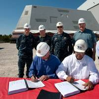 Jonathan Graves (sitting, left) and John Fillmore (sitting, right) sign the delivery documents: Photo credit HII