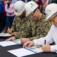 (Left to right) Cmdr. Robby Trotter, Cmdr. Scott Williams and Donny Dorsey sign the delivery document officially handing ownership of the destroyer Paul Ignatius (DDG 17) from Ingalls Shipbuilding to the U.S. Navy. Trotter is the ship's prospective commanding officer; Williams is the DDG 51 program management representative for Supervisor of Shipbuilding, Gulf Coast; and Dorsey is Ingalls' DDG 117 ship program manager. Photo by Derek Fountain/HII