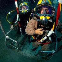 Lt. Cmdr. Bobby Greene, a Naval Reservist assigned to Explosive Ordnance Disposal Operational Support Unit (EODOSU) 7, right, and Chief Equipment Operator Mark Hurley, assigned to Underwater Construction Team (UCT) 2, stand on a stage that will take them back to the surface during a dive supporting Navy Dive Global Fleet Station 2008 off the coast of St. Kitts. (U.S. Navy photo by Senior Chief Mass Communications Specialist Andrew McKaskle)