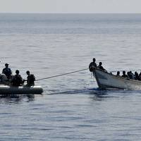 Members from the guided-missile cruiser USS Lake Champlain (CG 57) tow a disabled skiff carrying 52 Somali migrants. (U.S. Navy photo by Daniel Barker)