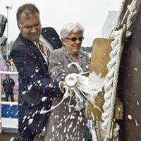 On June 5, 2010, Ellen Spruance Holscher and an unidentified man break a bottle of Champaign to christen the guided-missile destroyer Pre-Commissioning Unit (PCU) Spruance (DDG 111), during a ceremony at General Dynamics Bath Iron Works in Bath, Maine. Holscher is the ship's sponsor. Spruance is named after Holscher's grandfather, Adm. Raymond A. Spruance, the U.S. Navy commander at the Battle of Midway, fought June 4-7, 1942. (Photo courtesy of General Dynamics Bath Iron Works by D. Griggs)