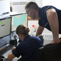 Petty Officer 3rd Class Sean McCoy conducts radio communications with Fireman Jaiden Barnhart, a watchstander at the station, in the station's communication room, July 30, 2013. (U.S. Coast Guard photo by Seaman Bryan Sullivan)