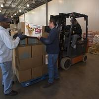 Newport News Shipbuilding employees Rudolph Johnson (left) and Wesley Dunlow (right) load boxes of donated food on to pallets at the Virginia Peninsula Foodbank. Foodbank employee Reginald Williams operates the forklift. Photo by John Whalen