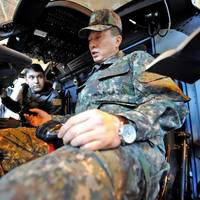 ROKN Commander Maritime Task Flotilla 7 Rear Adm. Kim Jongil, right, receives a brief inside an MH-60R Sea Hawk helicopter from Lt. Cmdr. Greg Nery assigned to Helicopter Maritime Strike Squadron (HSM) 77 (U.S. Navy photo by Kegan E. Kay)
